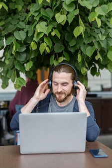 Man at a terrace listening to music on headphones with laptop