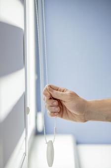 Man testing cassette roller blinds on windows.