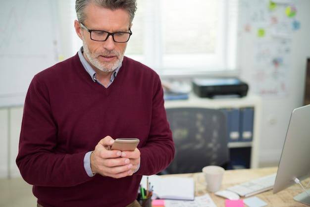 Человек текстовых сообщений во время его работы в офисе