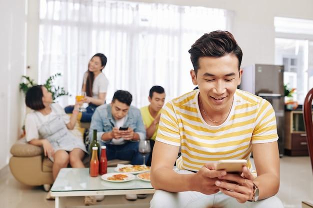 Man texting girlfriend at party
