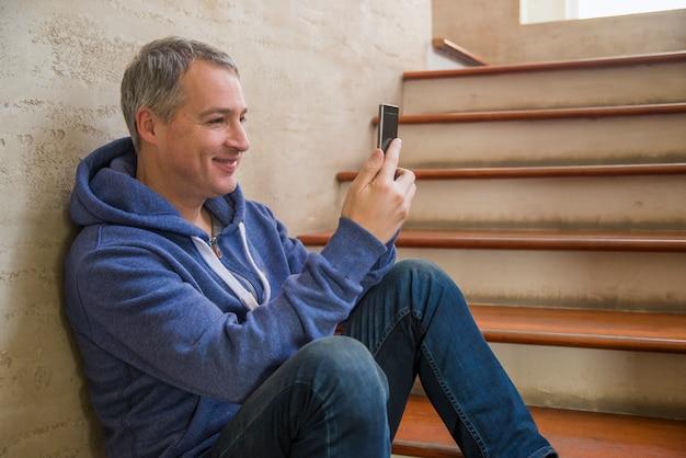 전화 남자 문자 메시지입니다. 사무실 건물 내부 행복 미소 스마트 폰을 사용하는 캐주얼 도시 전문 기업가. 계단에 모바일과 현대 성숙한 남자의 실내 초상화