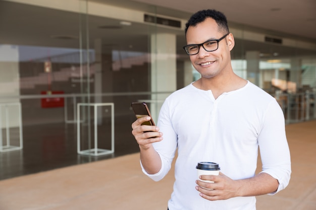 Man texting on phone, holding takeaway coffee, looking at camera
