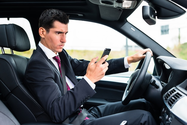 Man texting while driving by car