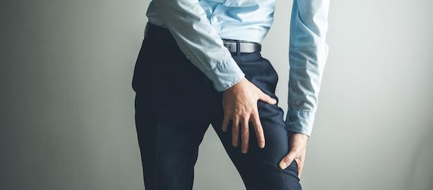 灰色の背景上のけいれんから男の太ももの痛み