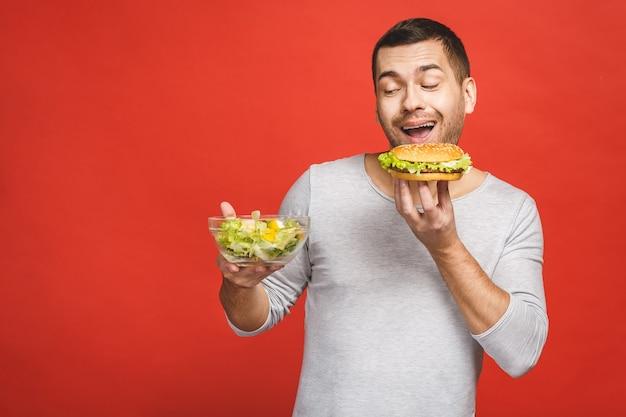 Человек думает, выбирая между салатом и гамбургером, здоровой и нездоровой пищей