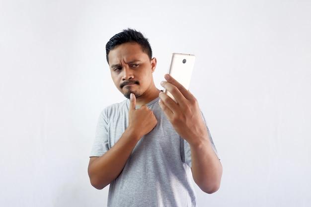전화를 보면서 생각하는 남자, 스마트폰을 들고 있는 사려깊은 소년 프리미엄 사진