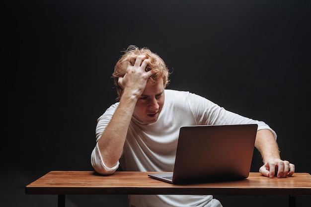 Человек думает на ноутбуке в белой футболке на черном фоне
