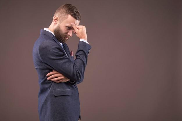 남자는 신중하게 손을 머리에 대고 숙고합니다.