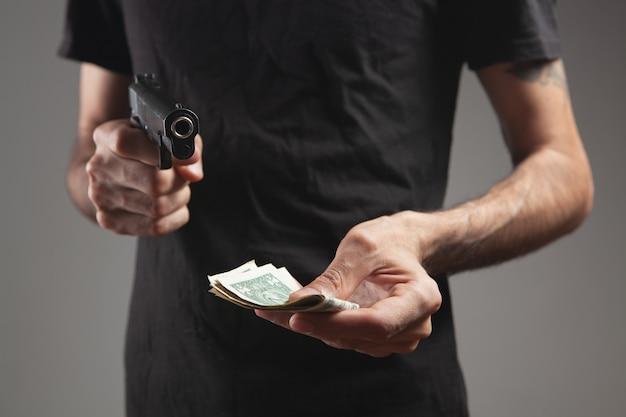 Человек, угрожающий оружием, берет деньги