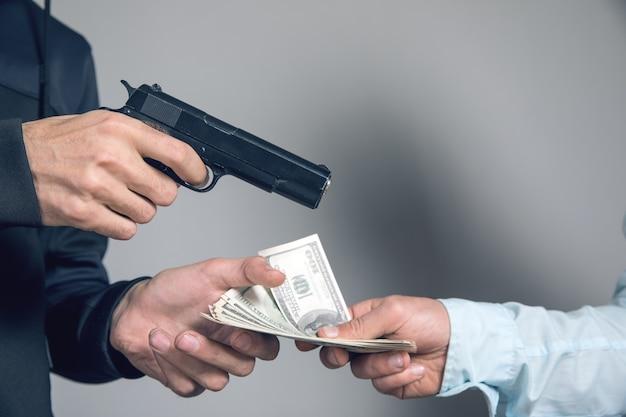 男は銃で脅し、ビジネスマンからお金を取ります