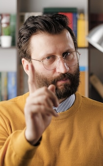 Man threatens with his finger. serious frowning bearded man in glasses in office or apartment room looking at camera and points menacingly with his index finger. close up view