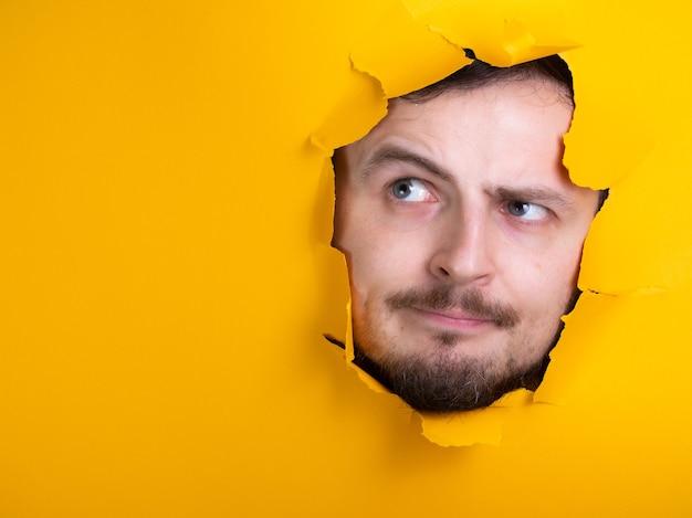 穴を通して男黄色い紙の思考