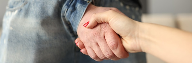 Man through fly on jeans shaking hands with woman close-up