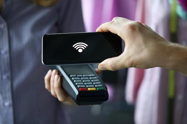 Человек через терминал, используя технологию pay pass