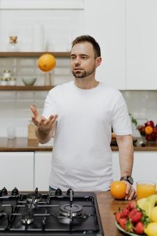 Человек бросает апельсин в воздух