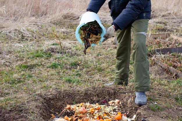 Мужчина выбрасывает остатки овощей и фруктов для компостирования на открытом воздухе в саду