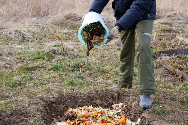 Man throwing away vegetable and fruit leftovers for composting outdoors in garden
