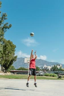A man throwing basketball in air