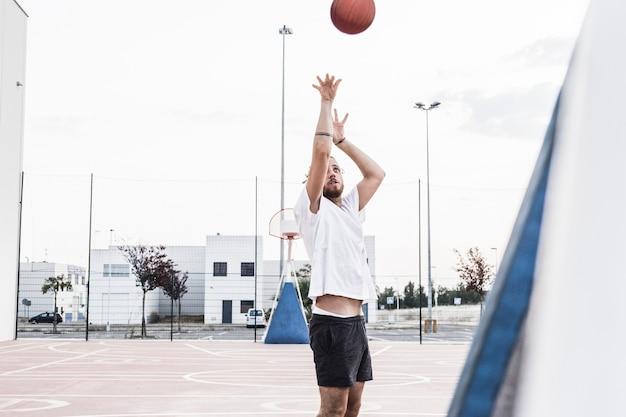 空中でバスケットボールを投げる男