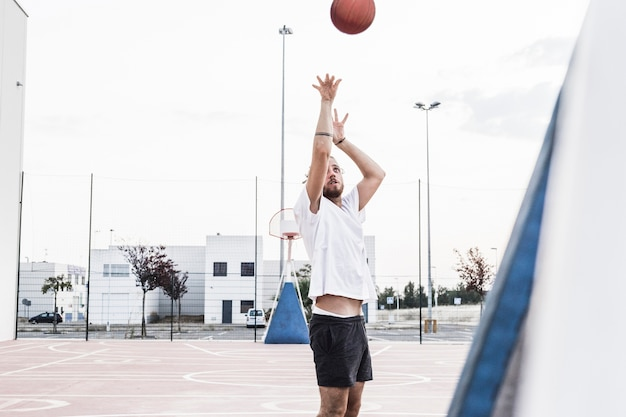 Man throwing basketball in mid-air