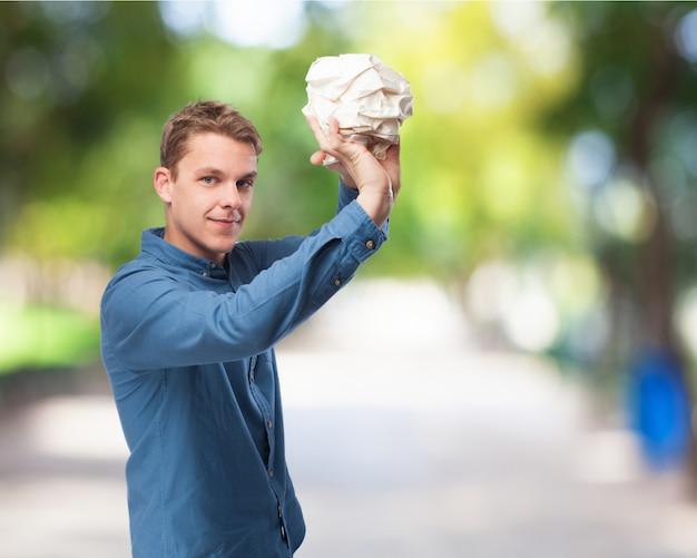 Uomo che getta una grande palla di carta