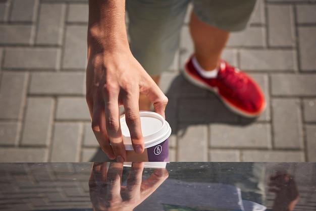 Человек бросает бумажную кофейную чашку в мусорную корзину