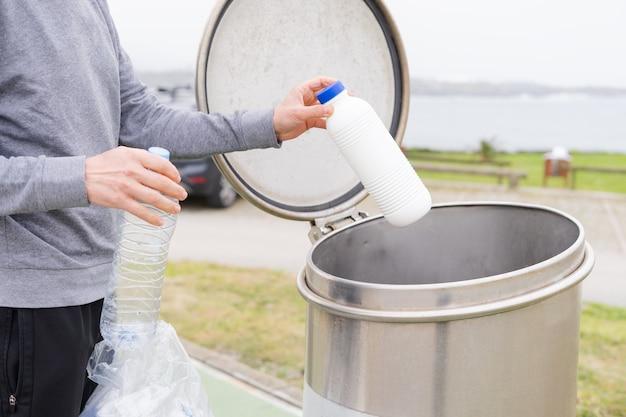 Человек бросает пластиковые контейнеры в пункт переработки пластика.