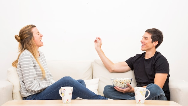 Man throwing popcorn in woman's mouth sitting on sofa