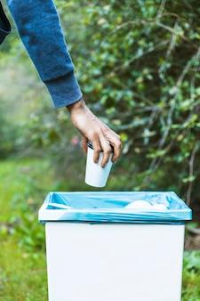 Человек бросает мусор в мусор