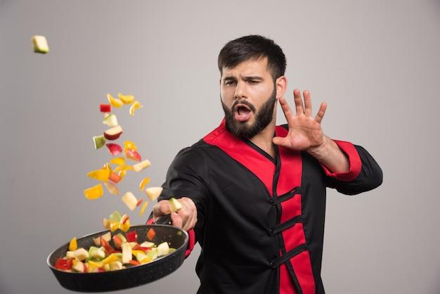 Uomo che getta le verdure dalla padella.