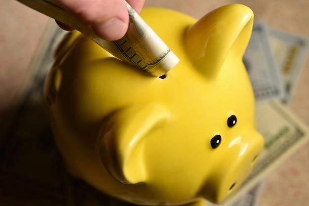 Man throws a bill into a yellow piggy bank.