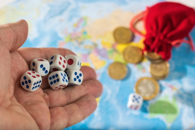 A man throws dice with red and blue markings on the world map
