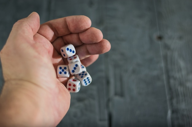 A man throws dice on wood table.