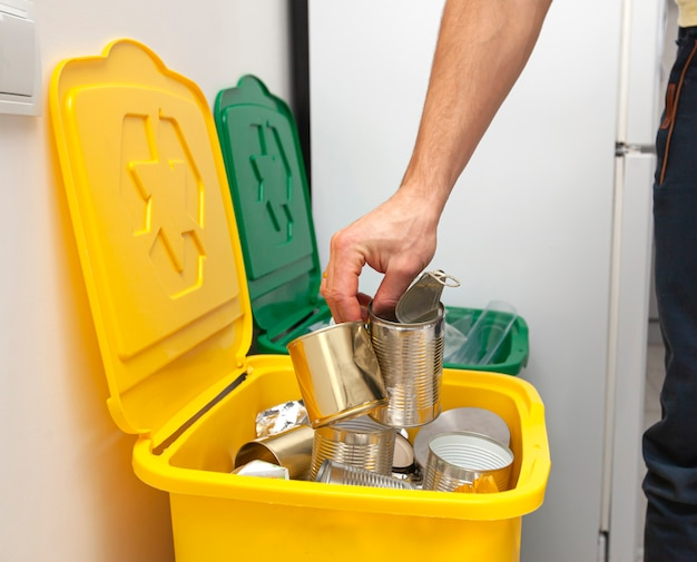 The man throws the tin can to the one of three container for sorting garbage
