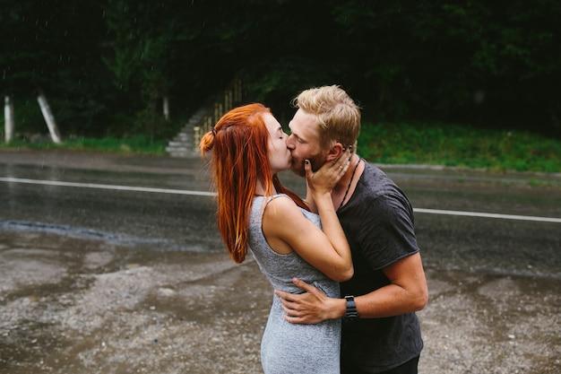 Мужчина подбрасывает свою девушку под дождем