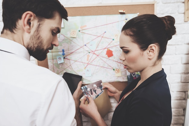 Man in tie and woman in jacket are looking at map.