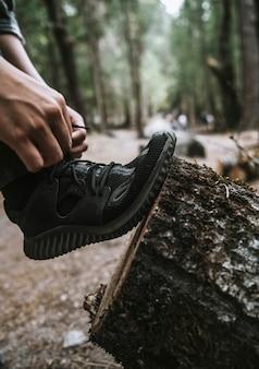 木の切り株に靴紐を結ぶ男