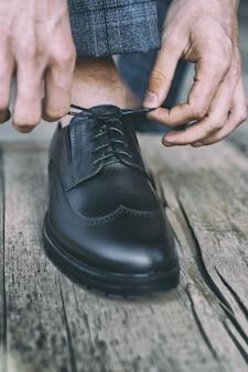 남자는 오래된 나무 바닥에 검은색 에나멜 가죽 신발에 신발끈을 묶고 톤 이미지