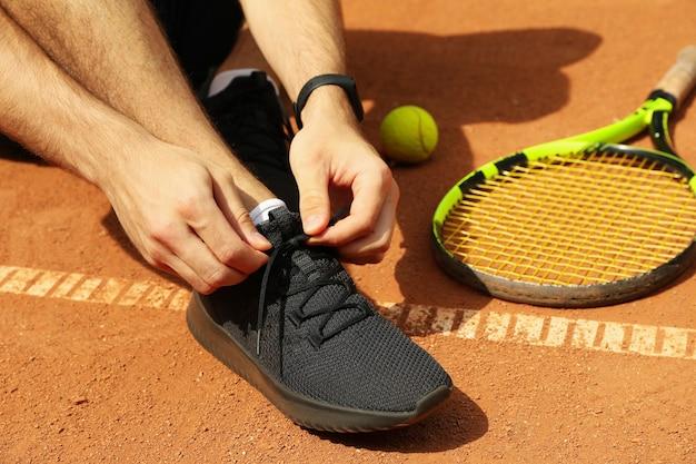 男はラケットとボールで粘土のコートに彼の靴ひもを結ぶ