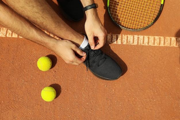 남자는 라켓과 공으로 클레이 코트에서 신발 끈을 묶습니다.