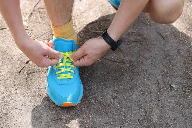 男はジョギングスニーカーの朝のジョギングの概念のひもを結ぶ