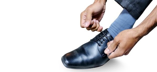 男は磨かれた靴に靴ひもを結びます。ビジネスフォーマルドレス