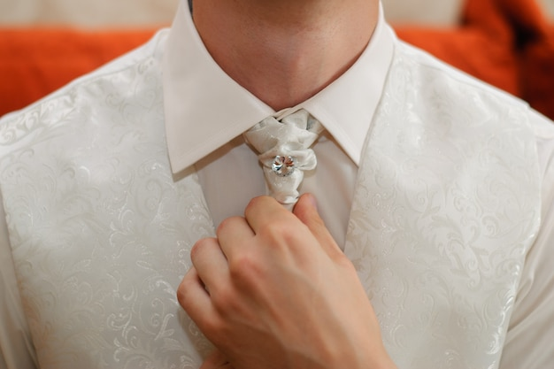 A man ties a white tie around his neck