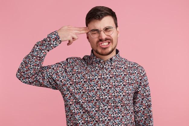 Усталый от неудач человек совершает самоубийственный жест, разочарованный во всем, стреляет в висок рукой, изолированной на розовом студийном фоне. расстроены мужские жесты в помещении, пытается покончить с собой
