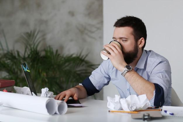 Uomo stanco al lavoro, bere caffè