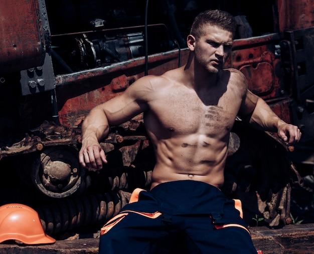 Человек усталый рабочий концепция сексуальный мужчина с обнаженным торсом отдыхает возле строительной техники или трактора на мускулистом рабочем