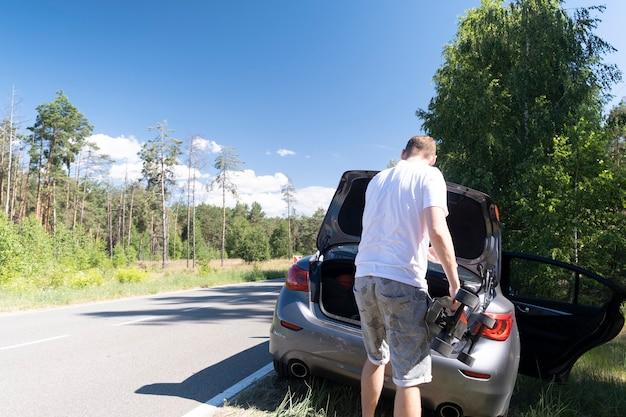 Мужчина достал скейтборд из багажника припаркованной у дороги машины в солнечный летний летний день