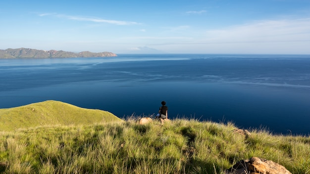 A man on the top of gili lawa darat island in the evening. komodo national park, indonesia