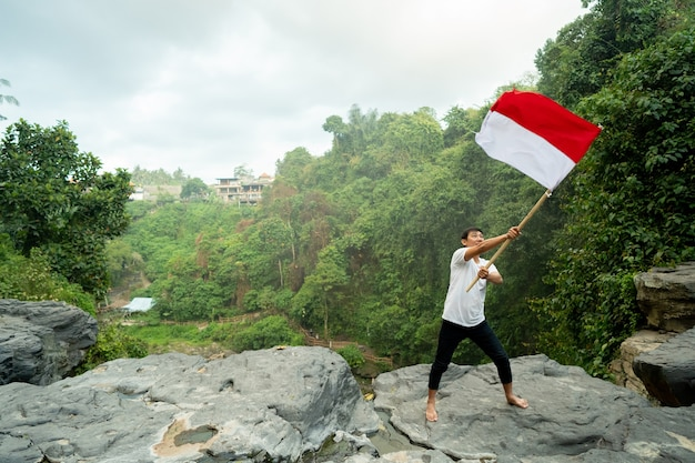 Man on top of the hill in the morning rising indonesian flag celebrating independence day
