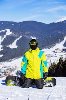 Man on the top of the hill with snowboard in sunny day. winter mountains